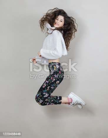 638678178 istock photo Cheerful young woman is jumping and having fun, studio shot 1223458446
