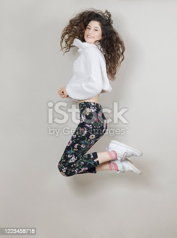 638678178 istock photo Cheerful young woman is jumping and having fun, studio shot 1223458718