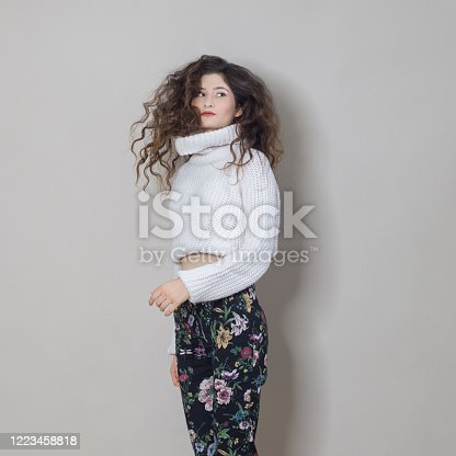 638678178 istock photo Cheerful young woman is jumping and having fun, studio shot 1223458818
