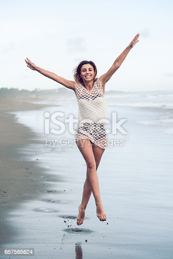 istock Cheerful Young Woman Jumping at the Beach with Raised Hands 657565624