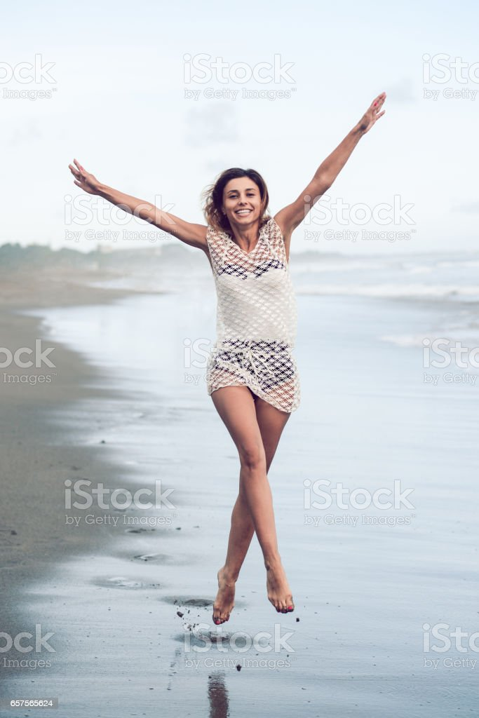 Cheerful Young Woman Jumping at the Beach with Raised Hands stock photo