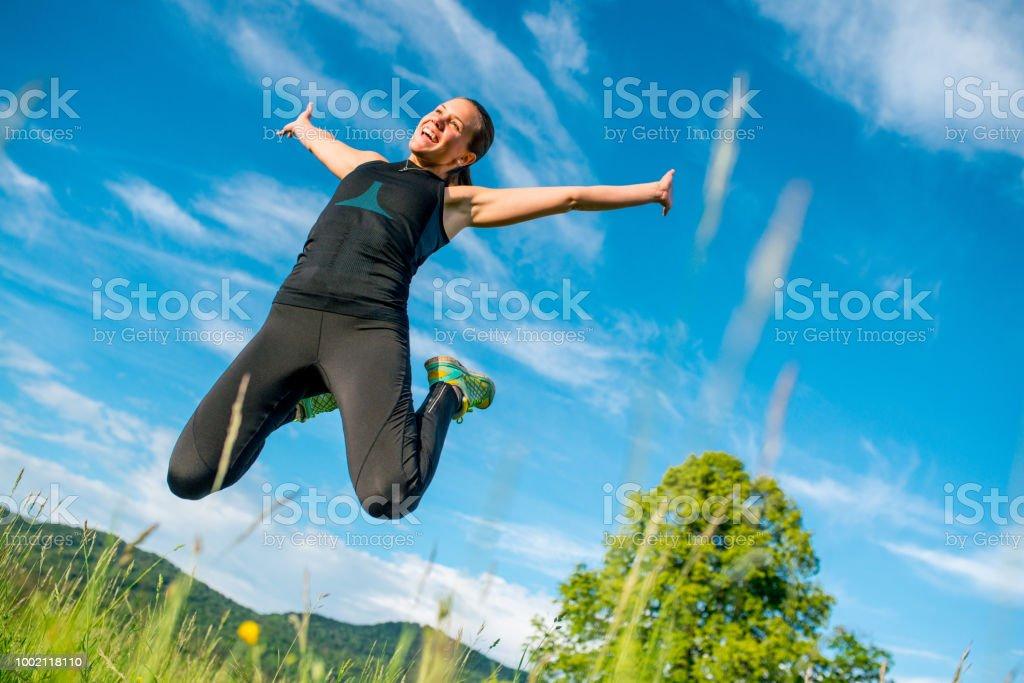 Bonne humeur jeune femme sautant en l'Air sur la Prairie - Photo