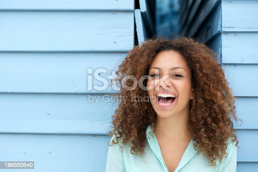 186534921 istock photo Cheerful young woman laughing outdoors 186550540