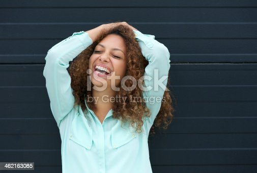 186534921 istock photo Cheerful young woman laughing with happy expression 462163085