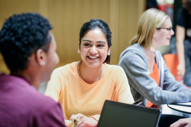 cheerful young woman listening to friend in college classroom, smiling - inghilterra foto e immagini stock