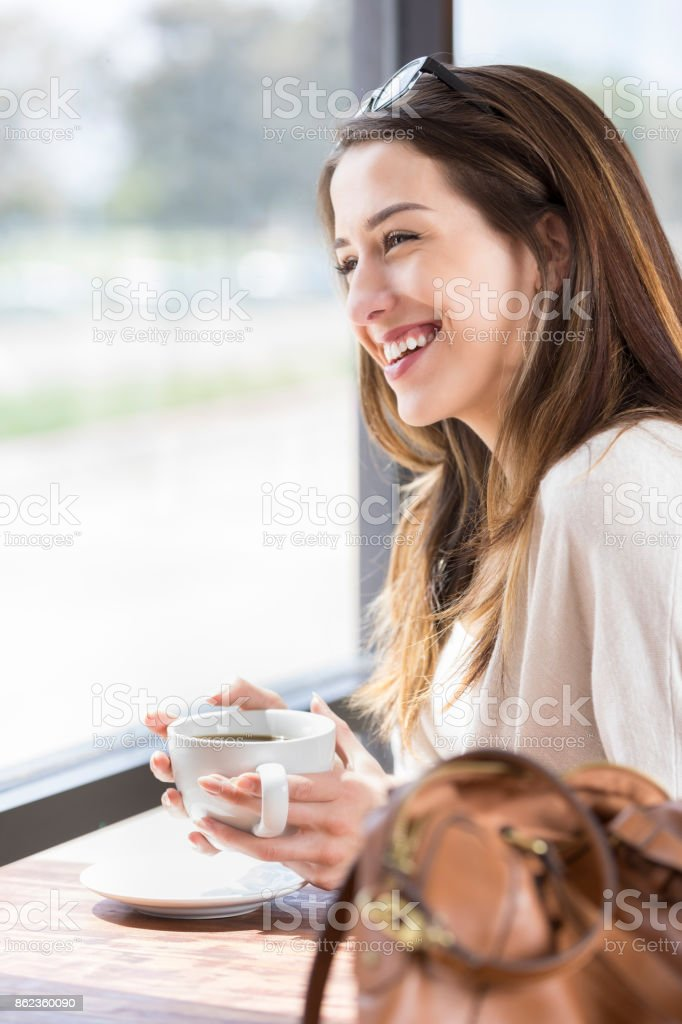 Cheerful young woman looks out window and drinks coffee stock photo