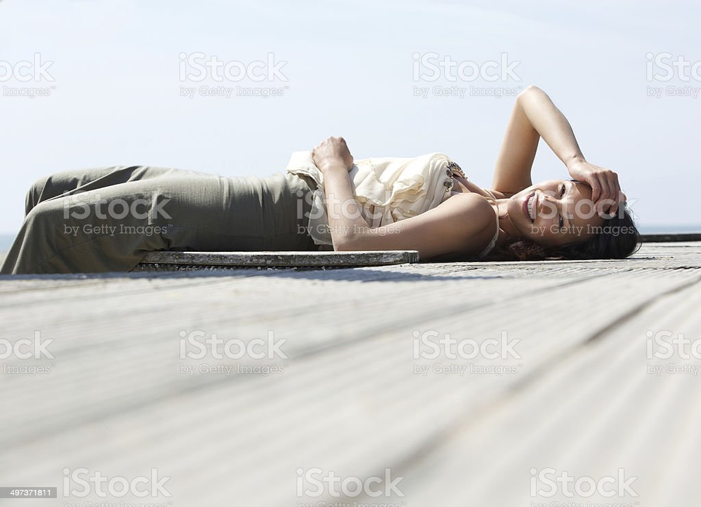Cheerful young woman lying down stock photo
