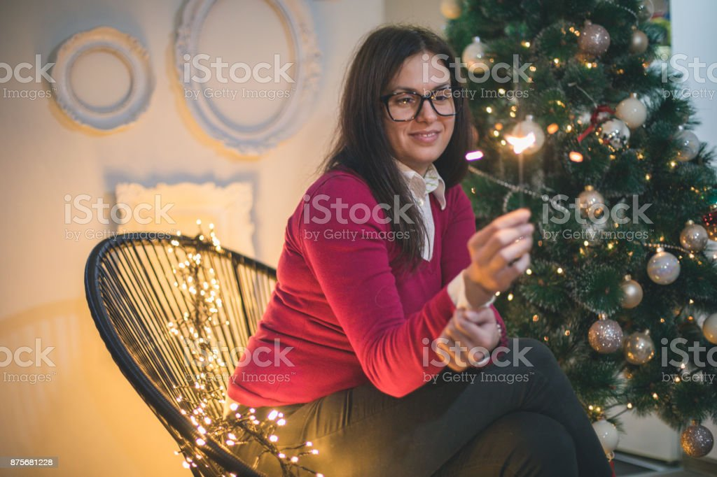 Cheerful young woman on home decorated for Christmas with sparkling...