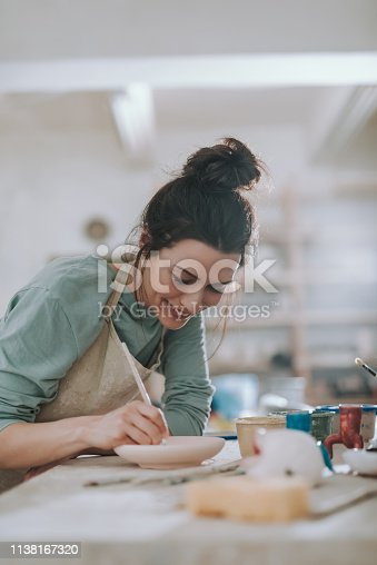 Beautiful brunette lady in apron drawing on ceramic plate and smiling
