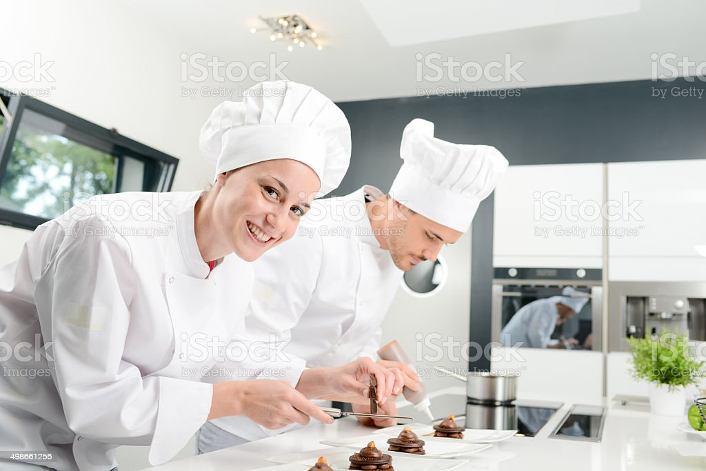 cheerful young woman professional pastry cook at work stock photo