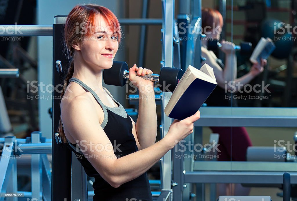 Cheerful young woman reading book in gym royalty-free stock photo