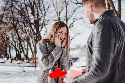 518335358 istock photo Cheerful young woman receiving a gift from her boyfriend 1133361268