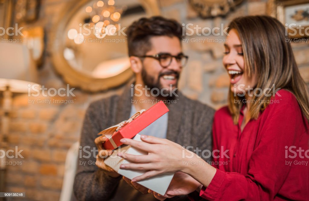 Cheerful young woman receiving a gift from her boyfriend. stock photo