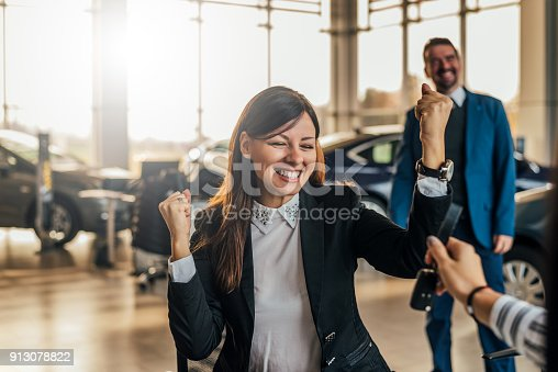 istock Cheerful young woman receiving the keys of her new car at car dealership. 913078822