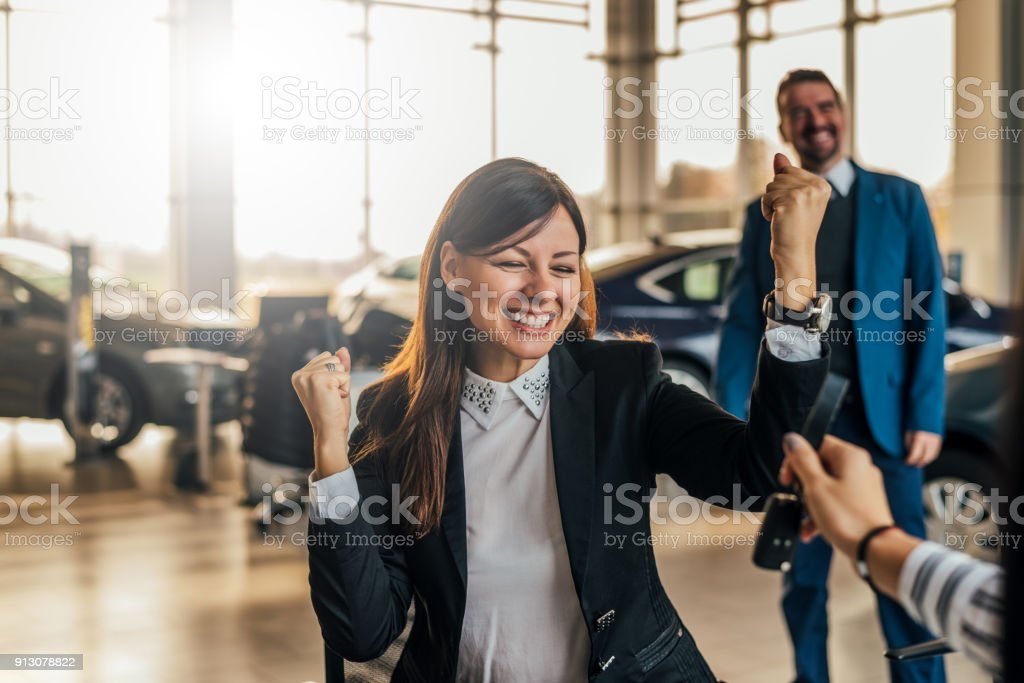Cheerful young woman receiving the keys of her new car at car dealership. stock photo