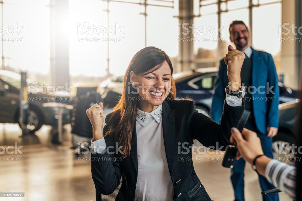 Fröhliche junge Frau Erhalt der Schlüssel ihres neuen Autos im Autohaus. – Foto