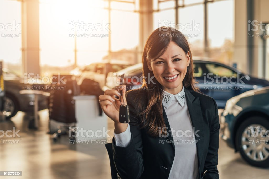 Cheerful young woman showing her new car key at dealership. stock photo