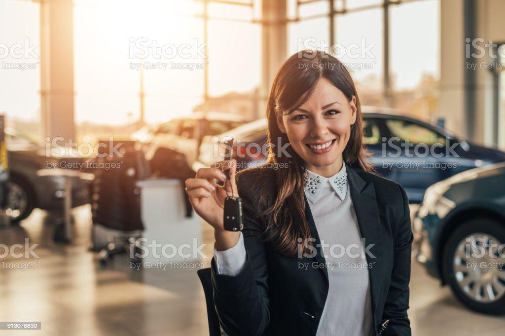 Fröhliche junge Frau zeigt ihre neuen Autoschlüssel beim Vertragshändler. – Foto