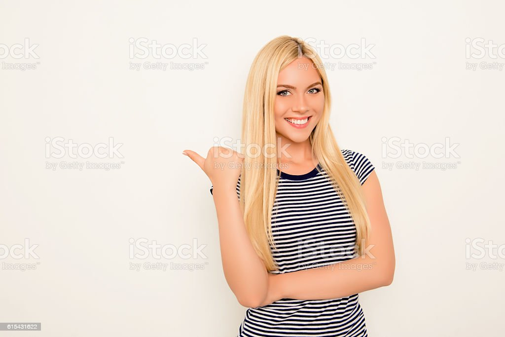 Cheerful young woman showing way on white background stock photo