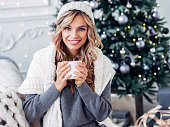 Cheerful young woman sitting near Christmas tree