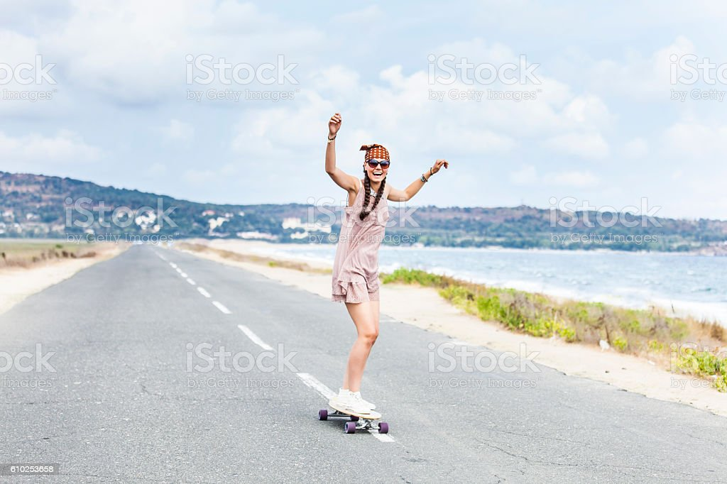Cheerful young woman skateboarding on road next to the sea stock photo