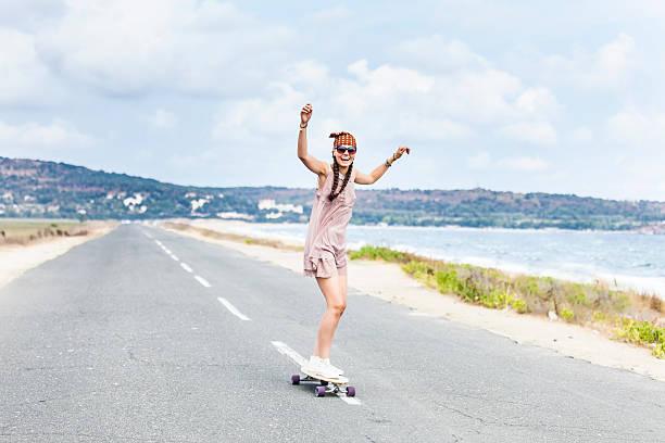 cheerful young woman skateboarding on road next to the sea - hippie stirnbänder stock-fotos und bilder