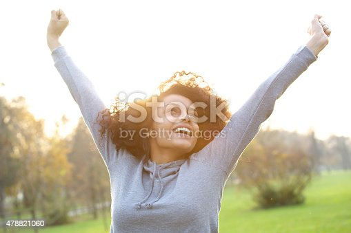 istock Cheerful young woman smiling with arms raised 478821060