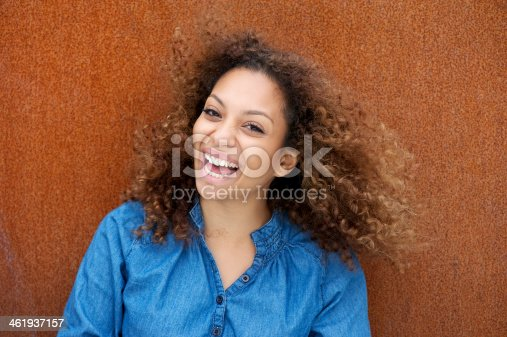 186534921 istock photo Cheerful young woman smiling with curly hair 461937157