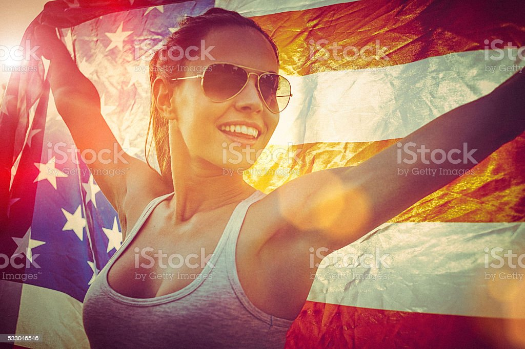 Cheerful young woman standing in a meadow holding american flag stock photo