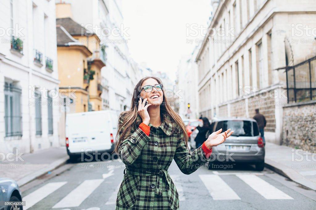 Alegre mujer joven de pie por la calle y hablando en el teléfono foto de stock libre de derechos