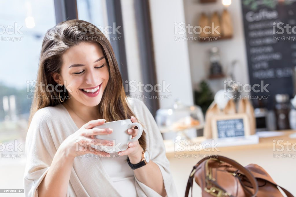 Cheerful young woman studies coffee cup during coffee break stock photo
