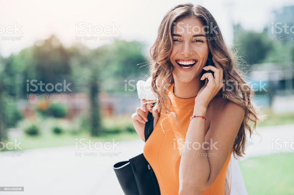 Cheerful young woman talking on the phone at sunlight stock photo