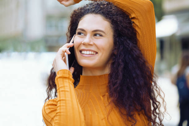 Cheerful young woman talking on the phone stock photo