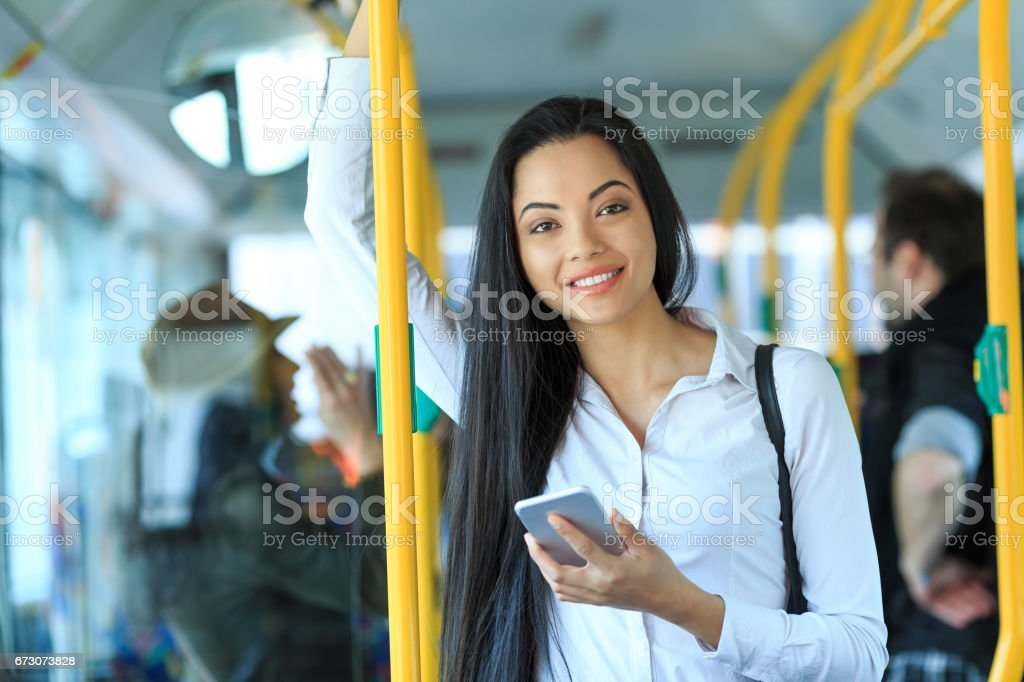 Cheerful young woman traveling and using smart phone stock photo