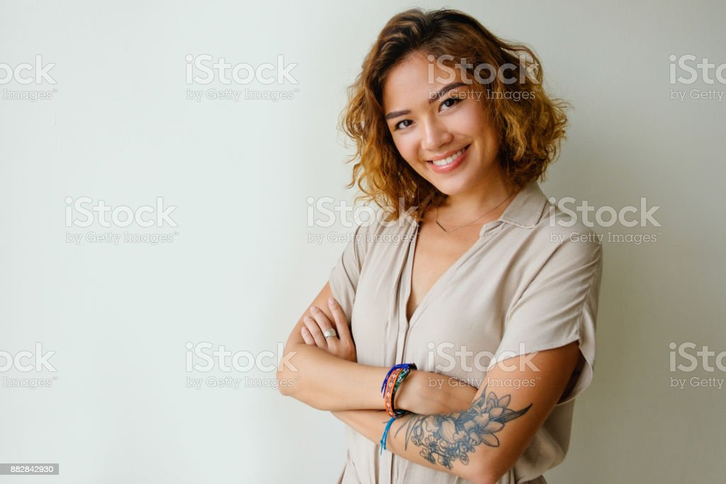Cheerful young woman wearing dress in studio stock photo