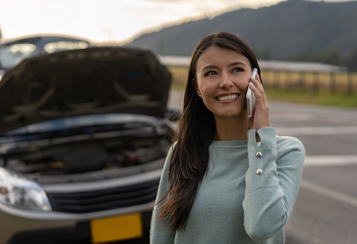 Cheerful young woman with car troubles calling for roadside assistance - Insurance concepts