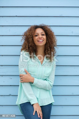 186534921 istock photo Cheerful young woman with curly hair laughing outdoors 461871409
