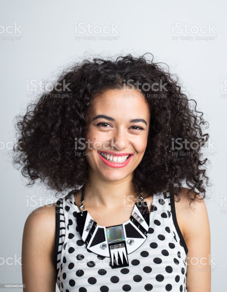 Cheerful young woman with curly hair Close up portrait of cheerful young woman looking at camera on white background 20-24 Years Stock Photo