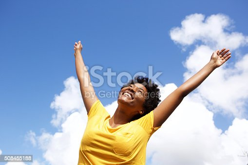 istock Cheerful young woman with hands raised towards sky 508455188
