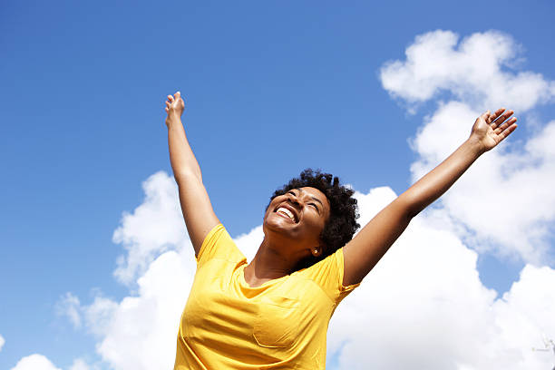 cheerful young woman with hands raised towards sky - arms outstretched stock photos and pictures