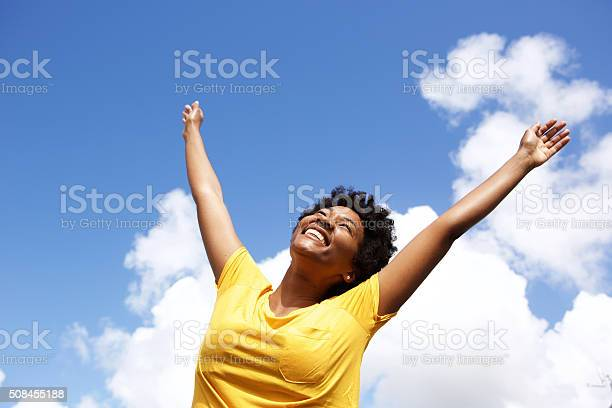 Photo of Cheerful young woman with hands raised towards sky