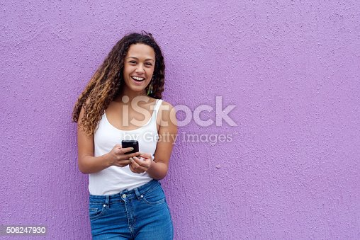 Cheerful young woman with a mobile phone standing against wall with copy space