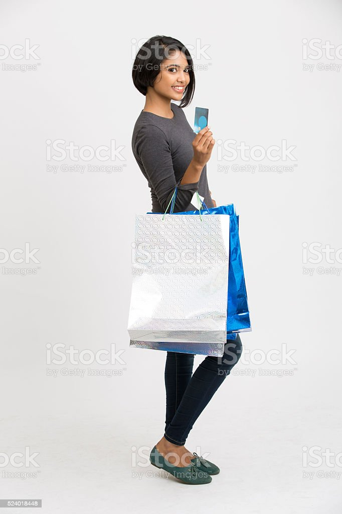 Cheerful young woman with shopping bags and credit card stock photo