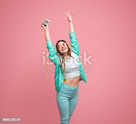 istock Cheerful young woman with smartphone 996028318