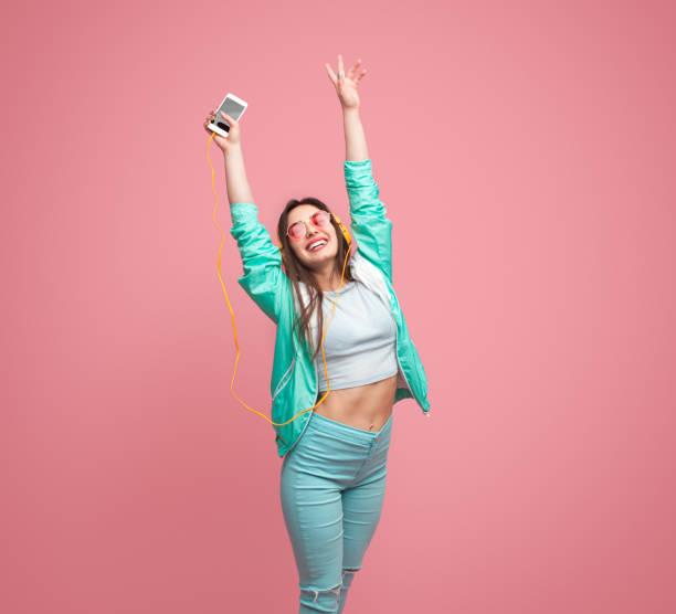 fröhliche junge frau mit smartphone - dynamische posen stock-fotos und bilder