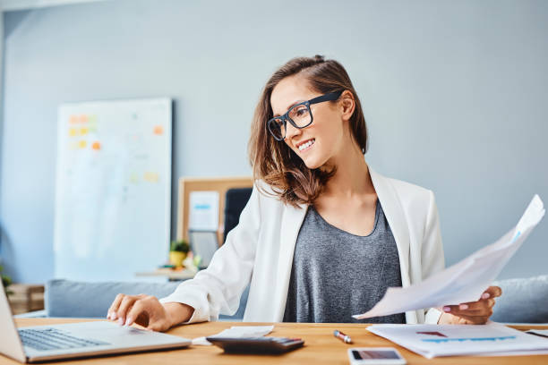 Cheerful young woman working with laptop and documents stock photo