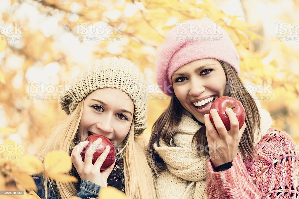 Cheerful young women eating an apple royalty-free stock photo