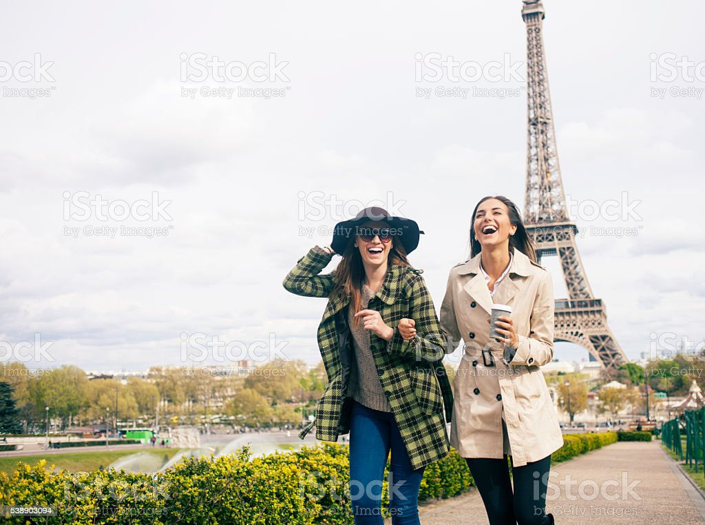 Cheerful young women having fun in front of Eiffel Tower stock photo