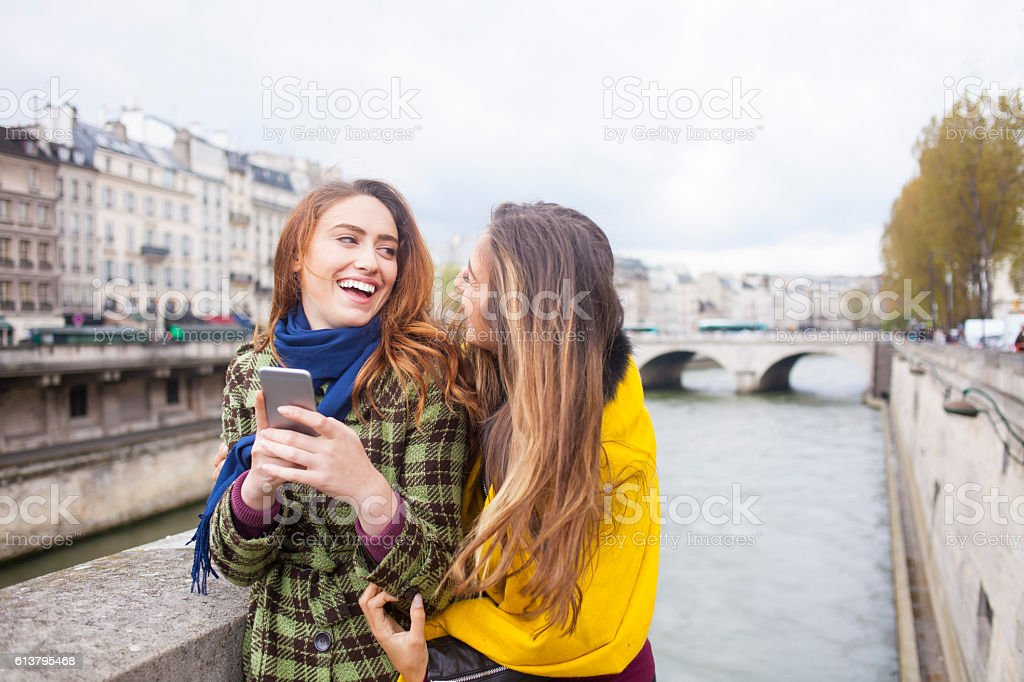 Cheerful young women using smart phone on a bridge stock photo