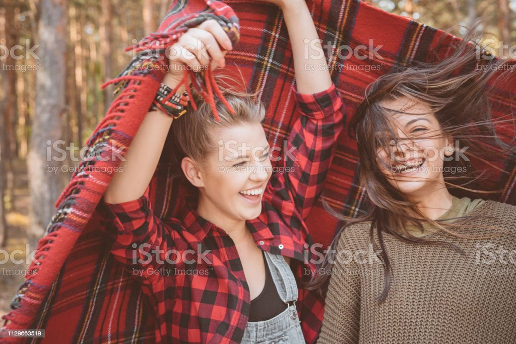 Cheerful young women wrapped in red blanket Cheerful beautiful young woman holding red blanket by friend with tousled hair. Female hipsters are in forest. They are spending summer vacation. 20-24 Years Stock Photo